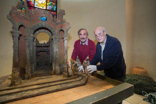 Klaus Zabrodsky und Otto Nester beim Aufstellen der restaurierten Osterrieder-Krippe in der Pfarre Mariahilf in Bregenz.
