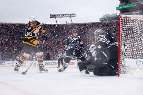 Boston-Stürmer David Pastrnak erzielt beim NHL-Winter-Classic gegen Chicago-Torhüter Cam Ward den Treffer zum 1:1-Ausgleich.ap