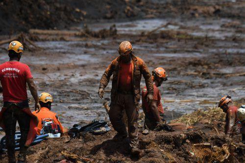 Einsatzkräfte suchen noch im Schlamm nach den Vermissten. AFP