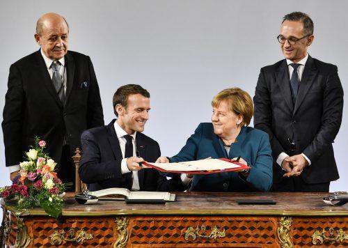Emmanuel Macron und Angela Merkel unterzeichnen den neuen Pakt. ap