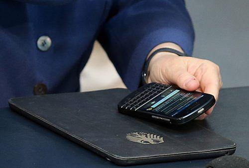 Während der Bundestagssitzung im Reichstagsgebäude in Berlin hat Kanzlerin Angela Merkel ihr Mobiltelefon vor sich. apa