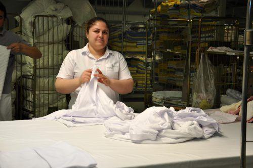 Die saubere Wäsche wird in Handarbeit zusammengelegt.FEIDER