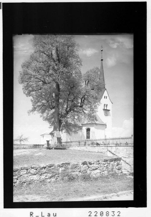 Die Kirche wird vom Friedhof und dessen Mauer umschlossen.