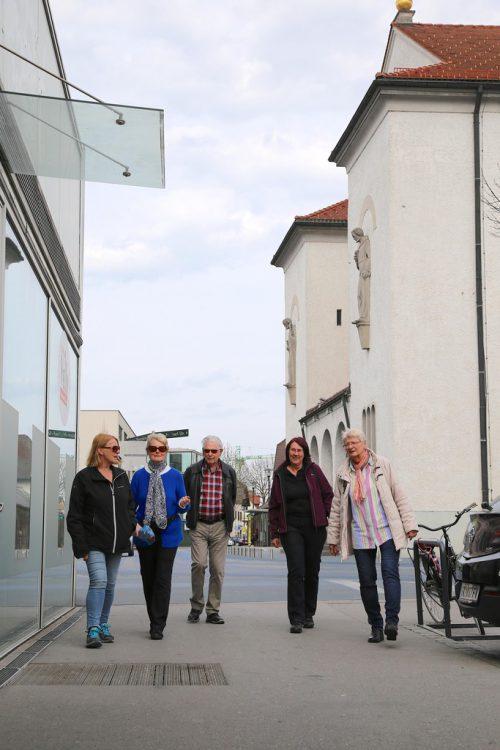 Menschen mit und ohne Demenz spazieren gemeinsam.
