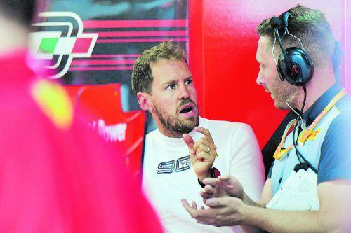 Sebastian Vettel diskutiert mit einem Techniker von Reifenhersteller Pirelli, von der Hand des Frischverheirateten blitzt ein Ehering.apa