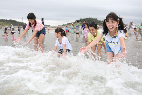Japanische Kinder planschen nahe der Atomruine im Meer. afp