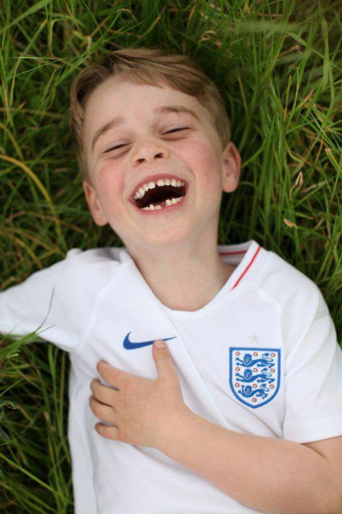Prinz George lacht im Garten des Kensington-Palastes ausgelassen mit einer kleinen Zahnlücke - in einem Shirt der englischen Fußball-Nationalmannschaft. Reuters