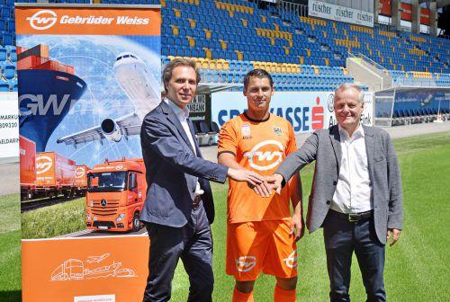 SCRA-Vizepräsident Werner Gunz (r.) und Wolfram Senger-Weiss präsentieren mit Martin Kobras das neue Goalie-Trikot von Premium-Sponsor Gebrüder Weiss.
