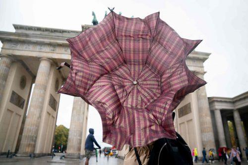 In Berlin kämpften Passanten am Berliner Tor mit ihren Regenschirmen, während in und um Hamburg Straßen unter Wasser standen. AFP