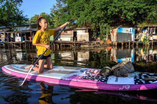 Ralyn Satidtanasarn, genannt Lilly, sammelt Müll aus einem verdreckten Kanal. AFP
