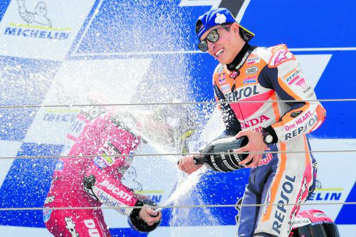 Sieger Marc Marquez deckt Andrea Dovizioso nach dem Grand Prix von Aragon mit einer Champagnerdusche ein.apa