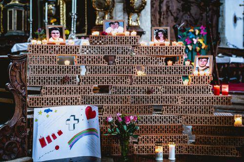Auf einer Klagemauer aus Ziegelsteinen sind Fotografien der Opfer aufgestellt.apa