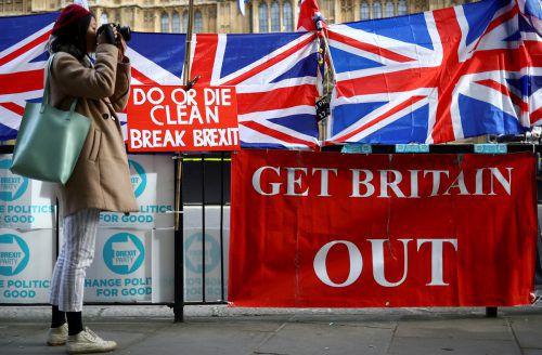 Eine Frau fotografiert vor dem britischen Parlament Plakate, die für einen raschen Austritt werben. Reuters