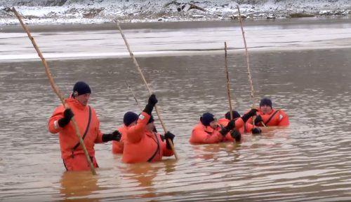 Einsatzkräfte suchen in dem Wasser nach Leichen. AP