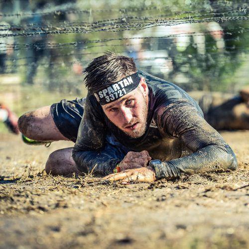 Hobbyathlet Matthias Ganahl kriecht unter einem 50 Meter langen Stacheldrahthindernis durch. Das ist nur eine Herausforderung unter vielen. Sportograf