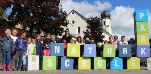 """""""Ouvertüre"""" zur Projektvorstellung – mit Buchstabenwürfeln deklarierten sich Schulkinder mit Dir. Sutterlüty und Lehrerin Kathrin Fehr als """"Naturparkschule"""". STRAUSS"""