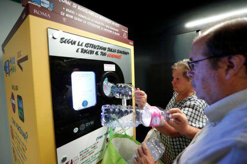 Passagiere stecken die Plastikflaschen in einen Automaten, der einem via App Geld für Tickets auf das Telefon lädt. reuters