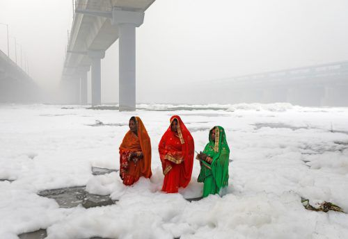 Drei Hindu-Frauen beten am 3. November während des Chatth-Puja-Festes im Fluss Yamuna im Schaum zum Sonnengott. Reuters
