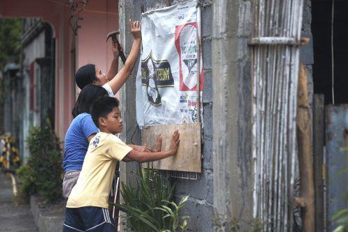 Bewohner bereiten ihre Häuser auf die Ankunft des Taifuns vor.ap