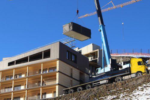 Box für Box wurde vom Tieflader über das fertiggestellte Haus A gehievt und auf die Fundamente des Hauses B geschafft. STRAUSS