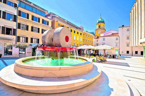 In der Mitte des Platzes thront der auffällige Brunnen des Architekten Igor Emili.
