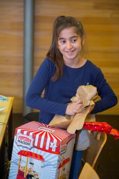 Jedes der dreizehn Kinder wurde bei der Weihnachtsfeier im Caritas-Lerncafé beschenkt. Havin, Simar und Aline freuen sich über eine Popcorn-Maschine, einen Fußballtisch und einen Riesen-Teddy. VN/Paulitsch