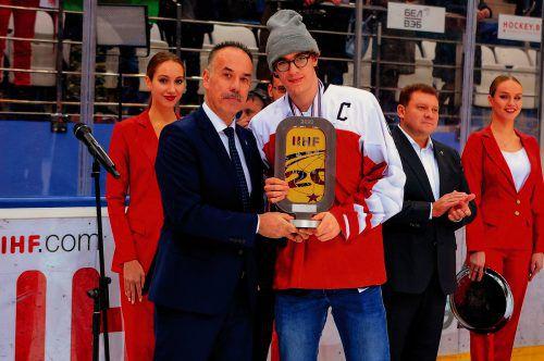 Kapitän Julian Payr bekommt von Igor Nemecek, Mitglied des Internationalen Eishockeyverbandes, die Trophäe für den Turniersieg überreicht. IIHF