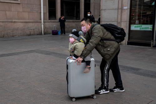 Aus Angst vor einer weiteren Ausbreitung des Coronavirus tragen diese Reisenden in Peking Gesichtsmasken. AFP