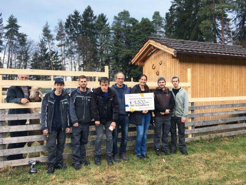 Das Fries-Projektteam und Beschäftigte der Lebenshilfe mitsamt Spendenscheck vor dem neuen Zaun.Lebenshilfe/Bolter-Matt