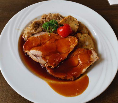 Der Schweinebraten mit Sauerkraut und Serviettenknödel.