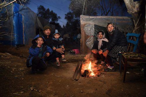 Eine Familie wärmt sich bei Minustemperaturen am Feuer. keck
