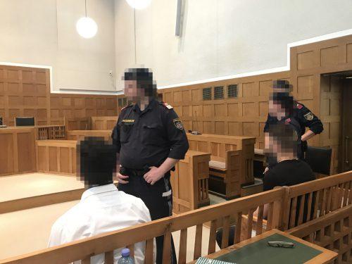 Justizwachebeamte mit zwei der insgesamt vier Angeklagten. hofer