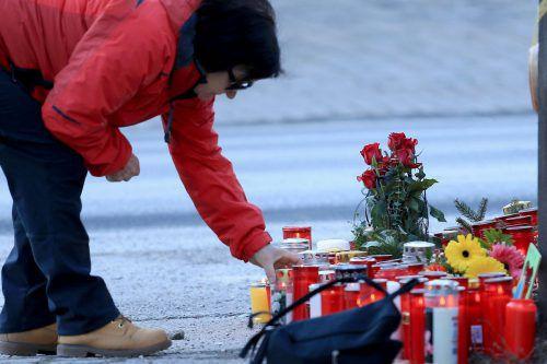 Trauernde legen Blumen nieder und zünden Kerzen an der Unfallstelle an. aFP