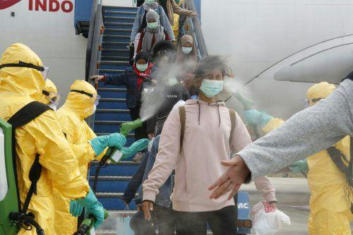 Auf vielen Flughäfen müssen sich China-Heimkehrer derzeit auf eine desinfizierende Dusche gefasst machen. Alex Hefel (r.) indes ist froh, dass er zwei virusfreie Wochen in Vorarlberg genießen kann. afP