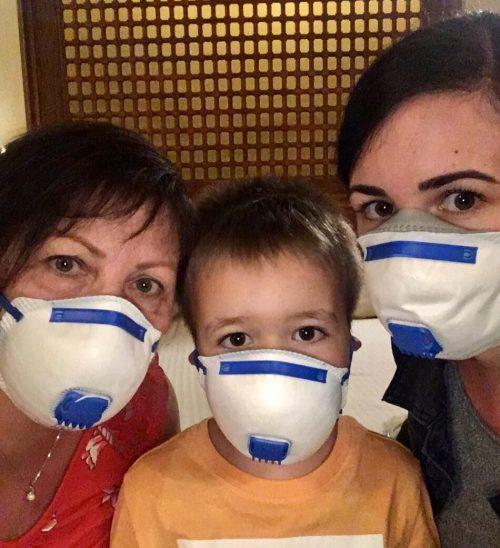 Atemschutzmasken für den Rückflug: Monika Mayer (r.) und ihreFamiliein Ägypten.