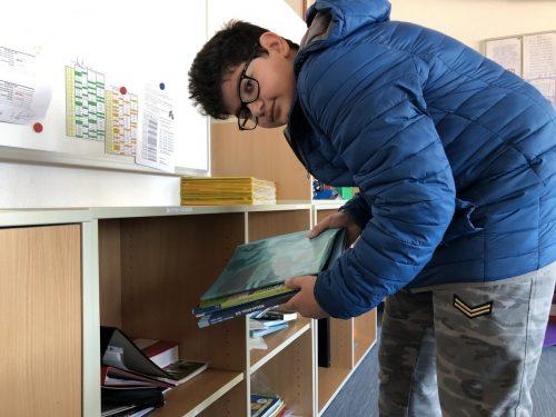 Bilal holt seine Übungsunterlagen aus seinem Schulfach. Die Lehrpersonen haben ihm alles feinsäuberlich hergerichtet.