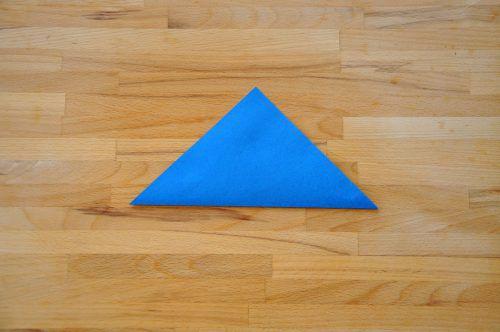 Das Papier (15 cm x 15 cm) vor sich auf den Tisch legen und die untere Ecke auf die obere Ecke falten, sodass ein Dreieck entsteht.