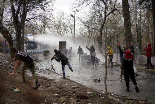 Die griechische Polizei wehrt die Menschen mit Wasserwerfern ab, diese antworten mit Steinen gegen die Grenztruppen. AP