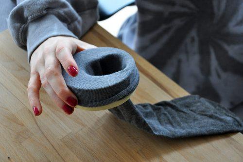 Die Socke über die Kleberolle stülpen.