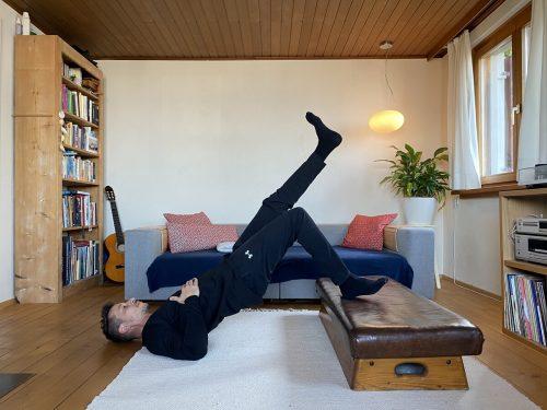 Einbeiniges Bridging mit erhöhtem bein. Stellen Sie einen Fuß auf eine Erhöhung. Heben Sie nun das Becken vom Boden ab. Variieren Sie die Beugung im Knie und spüren Sie den Unterschied. Passen Sie den Kniewinkel und die Erhöhung der Unterlage so an, dass sie gut zwischen 10 bis 15 Wiederholungen schaffen. Wechseln Sie das Bein und wiederholen die Übung 3 Mal hintereinander.