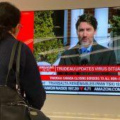 """<p class=""""caption"""">Eine Frau verfolgt die Verkündung neuer Maßnahmen durch Justin Trudeau.</p>"""