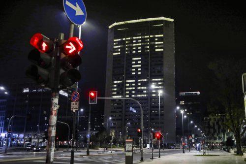 """Im menschenleeren Mailand wird ein Bürogebäude mit den Worten """"State a casa"""" (Bleib zu Hause) bespielt."""