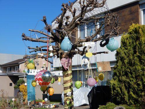 Kugeln und Ostereier hängen an bunten Bändern vom Baum.