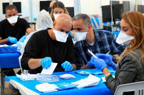 Mit Mundschutz zählen Wahlhelfer die Stimmzettel von Israelis aus, die derzeit unter häuslicher Quarantäne stehen.
