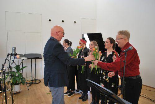 Musikschuldirektor Ivo Warenitsch verteilt Blumen an die Sänger.
