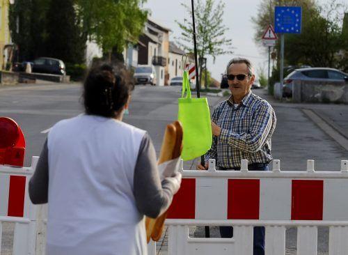Grenze? Kein Problem. Hartmut Fey kauft sein Baguette mit der Angel.AFP