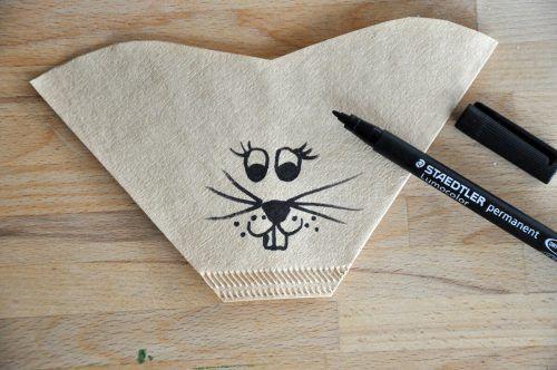 Mit dem Stift ein fröhliches Hasengesicht auf den Kaffeefilter zeichnen.
