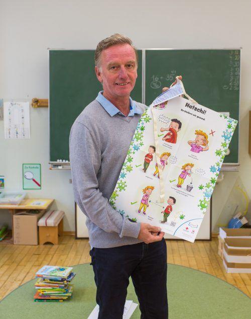 Christoph Jagg mit einem Plakat, das den Kindern die wichtigsten Regeln anschaulich in Erinnerung rufen soll.VN/Steurer.