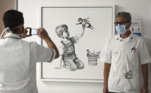 Die Krankenschwester auf dem Banksy-Gemälde trägt Umhang und Maske. AP