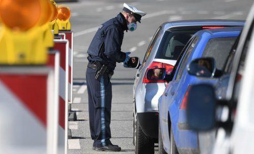 Ein Polizist kontrolliert Autofahrer an der Grenze zwischen Österreich und Deutschland. AFP